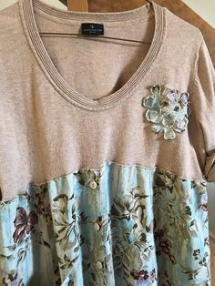 This upcycled tunic/dress is so soft and comfortable. Beautiful muted colors, the top is a soft sweater with a fun shabby flower attached, bottom flowing flowered material with buttons down the front and distressed funky jean pocket. Launders beautifully, so just slip it on and