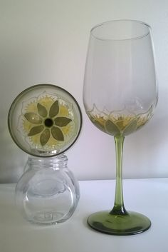 A set of hand painted wine glasses with a green and gold floral design.