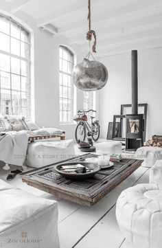 Totally white living room with rustic wooden coffee table and white sofas. Amazing perforated metal globe light-shade hanging above.