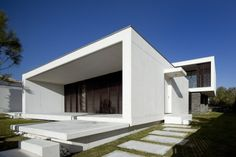 This portal for this villa in Portugal serves as a terrace in front of a louvered glass wall. The superminimal expression of the whole design means the portal reads as a dark rectangle among the white walls.