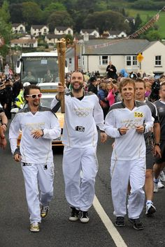 Torchbearer 106 Matt Bellamy, Dominic Howard and Christopher Wolstenholme, MUSE, carry the Olympic flame on the leg between Torquay and Teignmouth.