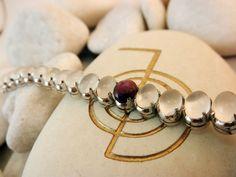 Pulsera artesanal de plata con una elegante combinacion de 28 gemas engarzadas de Adularia y una de Star Rubi. Precio: 90 Euros
