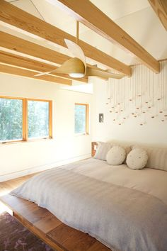 Eye-level windows in the master bedroom frame the forest views. Bud vases from CB2 filled with copper BB pellets form the raindrop-like installation above the bed. His-and-her face pillows add a whimsical touch.