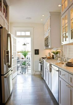 cabinets to ceiling on sink side for the homeless appliances Remodeled Row House - Traditional Home®