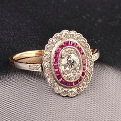 Platinum and Diamond Ring, set with an old European-cut diamond weighing approx. 0.25 cts., further set with diamond melee, and calibre-cut red stones, millegrain accents, 14kt gold shank,