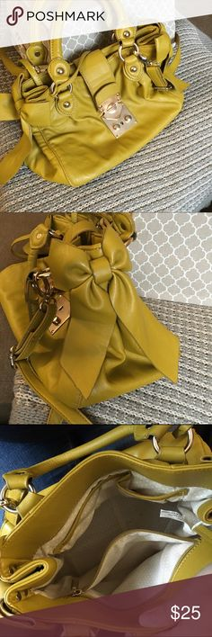 Charming Charlie yellow purse The color of this purse is gorgeous. It is so cheerful and perfect for summer. It has bows on either side as pictured. Also has a few pockets inside as shown. It also had a locket type thing that can close the purse. There is a pen mark on the back of the purse as shown I have not tried to get it out so it may come off. Charming Charlie Bags Crossbody Bags