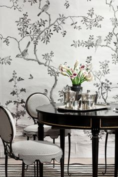 Black and white dining room features black and white chinoiserie wallpaper framing round black lacquer dining table with gold trim paired with black and white striped dining chairs over black and white striped rug.