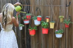 hanging garden for my back fence.  plants + plastic containers + spray paint + wire hangers + rebar + ladder hooks.  Easy way to make the back fence look adorable!!!