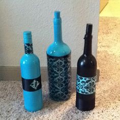 Used wine bottles spray paint, scrapbooking paper and ribbon to decorate! Looks so cute in my apartment! Easy and cheap!