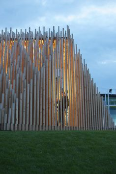 Pavilion made of vertical bamboo-like poles in layered arrangement