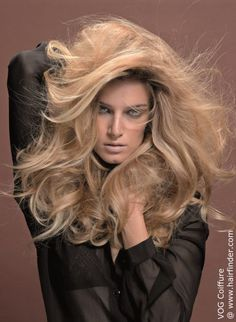 Release the wildness. Why be demure when your spirit is roaring and looking for outward expression? And you can even do this in style. Lots of it and oh, so voluminous! Go big with long layers, a lot of teasing to lift up   those roots – basically all of the tricks in the book were used to render this sleek long and layered look into a soufflé of passionate waves wavering inside of a golden halo. Long sweeping lines are essential to the   success of this seduction made of hair as is the…