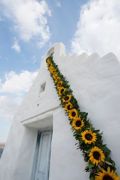 White orthodox chapel with lovely sunflowers decoration.  #weddingplannergreece