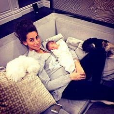 Danielle Jonas holds daughter Alena Rose Jonas while surrounded by her pet dogs.