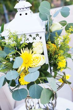 White lanterns with sunny blooms accented by eucalyptus leaves