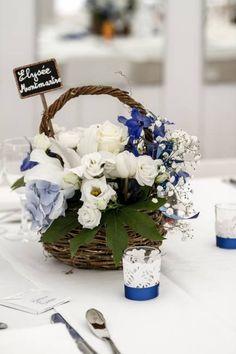 agence d'organisation de mariage normandie, centre de table dans un panier d'osier, fleurs blanches et bleu roi, nom de table, photophores en dentelles www.mariagedanslair.fr