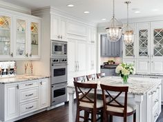 Detailed cabinetry with upper glass X door cabinets in stunning white adds character and charm to this immaculate kitchen.