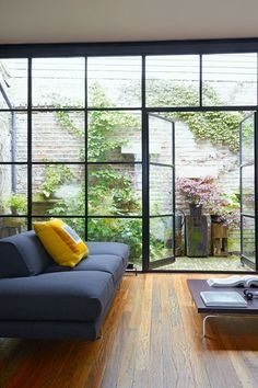 In this contemporary grey living room, an outdoor area was created by shortening the roof and adding a glass wall. (http://houseandgarden.co.uk)