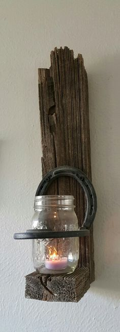 We tore down our kids old playset in the backyard, reclaimed some of the old wood welded to horseshoes together and with mason jars I already had in the cupboard I made two amazing wall sconces. easy DIY