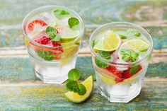 Summer lemonade or cocktail with lime, ice, strawberry and green mint in glass on rustic wooden table, mojito