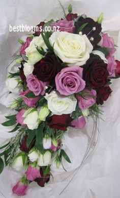 Trailing wedding bouquet of roses in ivory, burgundy and purple