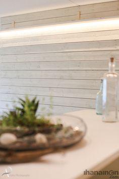 Ihanainen.com Raakalauta seinä on valaistu seinähyllyn taakse sijoitetulla lednauhalla, jolloin pinnan rouheus korostuu. #sisustussuunnittelu #tampere