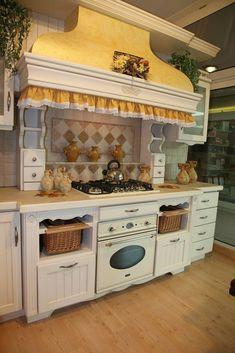 Cucina country in legno massello laccato bianco. Il piano è in marmo botticino con particolare gioco di piastrelle nello schienale. La cappa, bombata, è