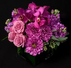 This is a floral arrangement that features roses, dahlias, stock and mokara orchids in a lavender and purple color scheme.