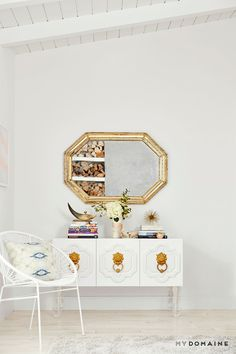 Peaceful corner in white bedroom with armchair, dresser, styled books and flowers, and gold mirror