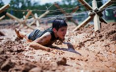 A boy crawls through mud at the inaugural Battlefrog Obstacle Course Race Series held at Georgia International Horse Park in the United States. The course was designed by Navy SEALs to recreate real-life challenges in the field.