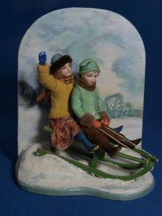 This is a 12th scale miniature model of two children playing on a sledge in a snow scene.These figures are hand sculpted ,painted and dressed in
