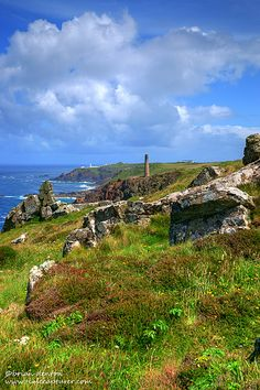 PENDEEN   Cornwall: 'Rocky granite outcrops and a view along the north Cornwall coast at the Pendeen headland with its distinctive white lighthouse at Pendeen Watch. In the foreground one of the chimneys of the Levant Mine complex which is now a museum.'     ✫ღ⊰n
