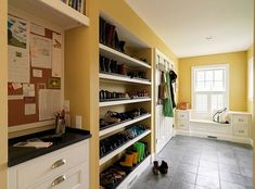 awesome mudroom design with shoe racks and clothes hangers. With shoe trays for messy shoes