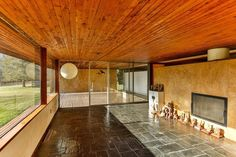 This midcentury living room has stone flooring, wood plank ceilings, marbled partition walls, walls of glass and beautiful views.