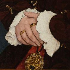 Dettagli 3. Hans Holbein il Giovane: Ritratto di Margaret Waytt, moglie del Cancelliere Henry Wyatt. Tempera all'uovo su tavola di quercia, del 1540. The Metropolitan Museum of Art, New York. I morbidi polsini coprono leggermente le mani inanellate: le aperture delle maniche, di due toni di marrone, sono chiuse con fusi d'oro, come d'oro è la medaglia appesa alla cintura.