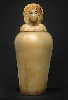 This canopic jar with a lid in the shape of a royal woman's head was found in an Egyptian pyramid. It is intracately carved and made of travertine(limestone), blue glass, and obsidian. It is believed to have been crafted during Akhenaten's reign, and the face on the lid has not yet been paired with a name. This artifact can be found in the Metropolitan Museum of Art.