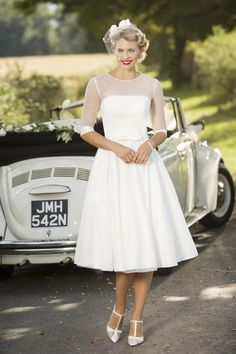 Bunny - This 1950's style strapless bridal gown is made from polka dot tulle with a straight neckline for an added retro edge. It can be worn with the sheer bolero as pictured and removed for the evening for a different look. The dress is finished with a zip up back and buttons and the bolero buttons to the nape of neck.