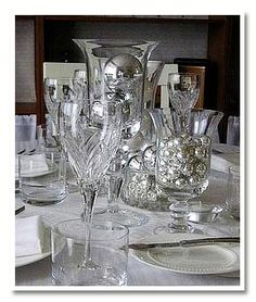 elegant and cheap idea for center pieces - those silver christmas balls are super cheap and you can get them in a lot of colors - we can get a ton of glassware at Goodwill...
