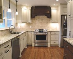 French country kitchen design - white cabinets in combination with granite counters, marble tile backsplashes, stainless steel appliances and a wooden floor