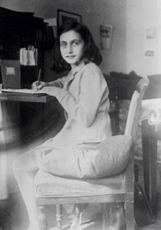 Anne Frank writing at her desk in her room in the Merwedeplein apartment, Amsterdam. Photo taken 1941.