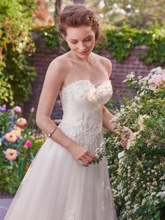 Rebecca Ingram - eleanor, This tulle A-line features lovely lace appliqués floating over a ruched bodice, sweetheart neckline, and eye-catching hem. Finished with covered buttons over zipper and inner elastic closure.