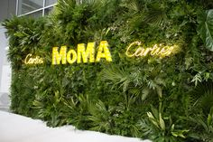 The arrivals backdrop—featuring the Cartier and MoMA logos rendered in neon and marquee lights—echoed the dense arrangements of tropical greenery...