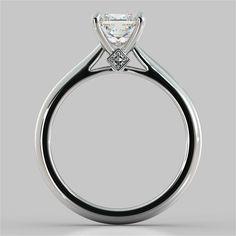 Presenting a princess cut brilliant solitaire in its purest beauty nestled on a cathedral setting with a peek-a-boo accent stone. The curves in the comfort fit band create a sensuous effect that will leave her feeling beautiful and elegant as she is.<br /> <br /> Exquisitely made to order according in your selection of precious metal, this Engagement Ring showcases a Princess Cut simulated diamond and can be customized to your specifications to accommodate a center stone from 1 to 3…