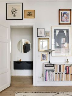 round mirror, low shelves, gallery wall in muted tones, wooden floors