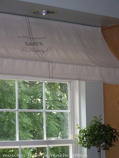 French awning window treatment; burlap or drop cloth stenciled with logo, tension rod through pocket at top, drape fabric over the bottom rod