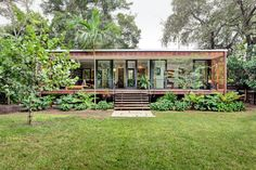 Melissa and Jacob Brillhart's house in Miami: sixteen Western red cedar shutters on the front of the house close to provide privacy and open to encourage cross-ventilation.