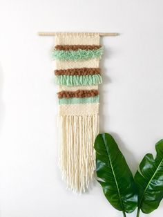 Handmade woven wall hanging with different textures, fibers, and colors. Dimensions: Length - 40 Width - 11 Wooden rod measures 18 across Custom