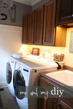 Wonderful laundry room makeover — shelf behind washer/dryer, under cabinet lighting, hanging baskets — WOW!