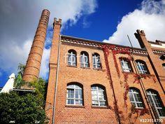 Restaurierte alte Fabrik mit Schornstein aus Backstein vor blauem Himmel mit Wolken an der Hansaallee in Münster in Westfalen im Münsterland