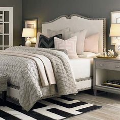 Dark paint color, white upholstered bed, light gray bedding with pops of a blush pink. To add a look of comfort and luxury, make sure you add textures to your bedding.