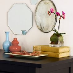 Use an Heirloom  Liberated from the china cabinet, a passed-down platter or plate becomes a dresser-top catchall you'll use every day. Add some personality by hanging an eclectic array of looking glasses — some new, some vintage flea market finds. Finish off the bureau area with shapely, vivid vases that become an instant collection when grouped together.